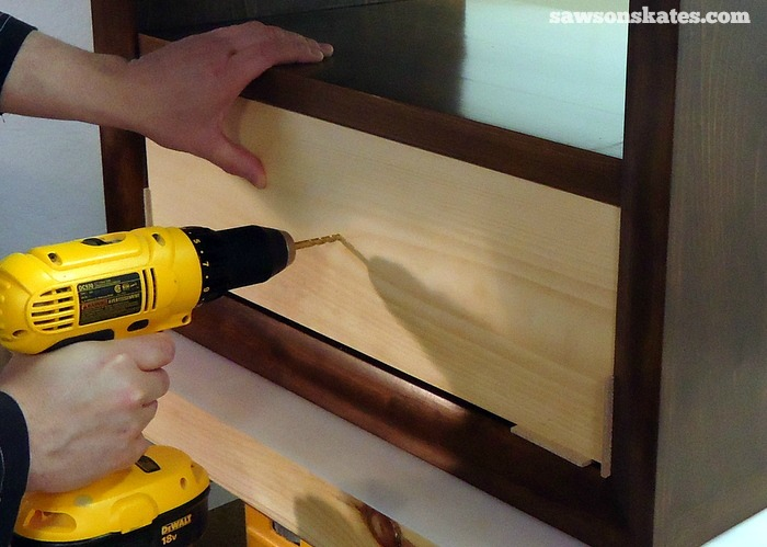 Place the Retro Nightstand drawer front in position and drill a hole through the drawer front into the drawer box. Attach the knob and using the scrap 1/8
