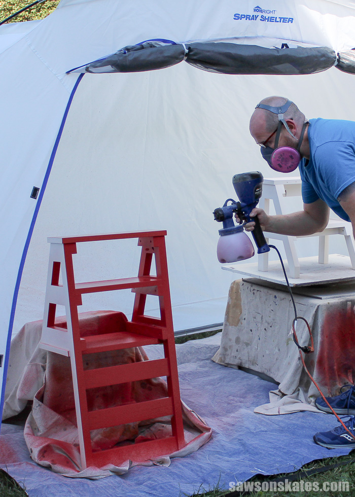 Using the spray shelter to spray paint a DIY ladder chair