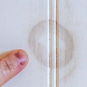 A wood knot bleeding through white paint