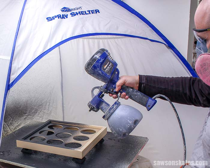 Spraying chalk-style paint with a sprayer inside a spray shelter