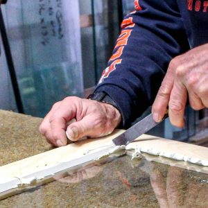 A putty knife is used to bevel windowing glazing