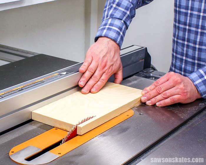 Using a table saw to cut a piece of 1×6 wood