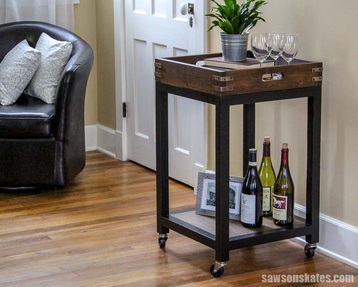 Build a DIY Bar Cart with these free plans! It's easy to make with your Kreg Jig and inexpensive wood. It features a removable tray and aged metal hardware.