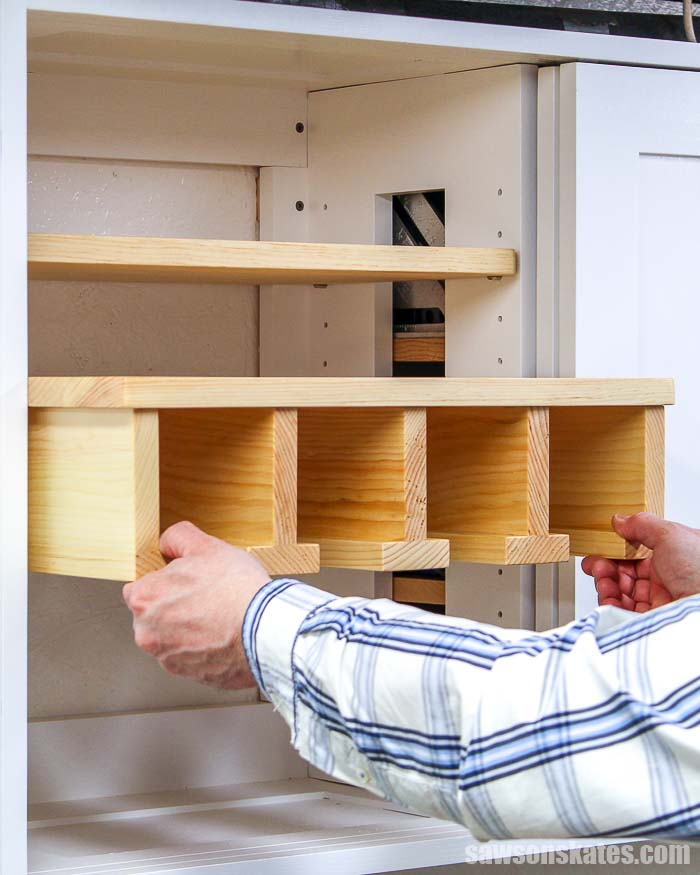 Sliding a cordless drill storage rack into a wall-mounted tool storage cabinet