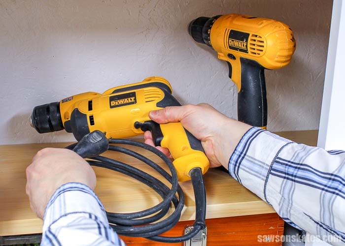 Placing a drill on a shelf in a tool storage cabinet