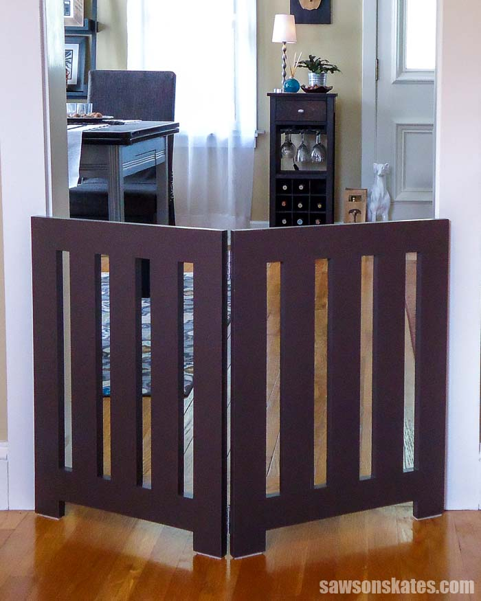 Learn how to make a DIY dog gate! This freestanding wood pet gate is perfect for doorways and stairs. It's easy for anyone to build with some simple tools.