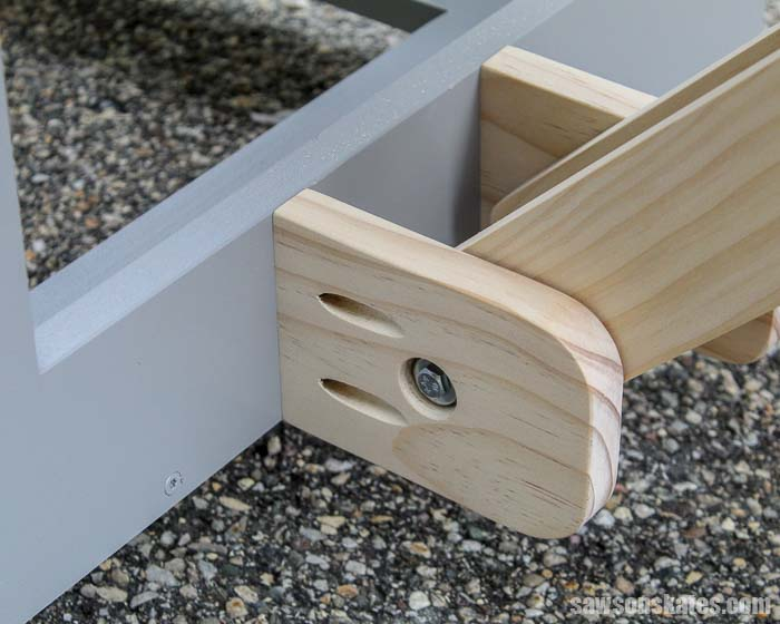 The folding arms of this DIY mobile miter saw station pivot on wooden anchors