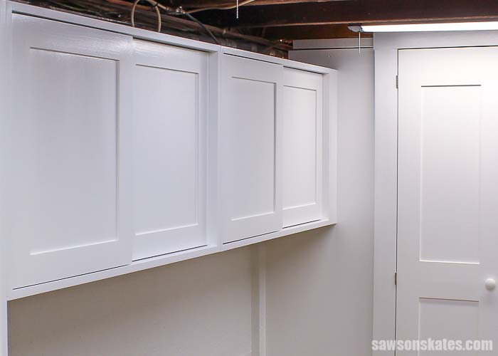 The DIY tool storage cabinets are painted white and installed on the wall in a small workshop