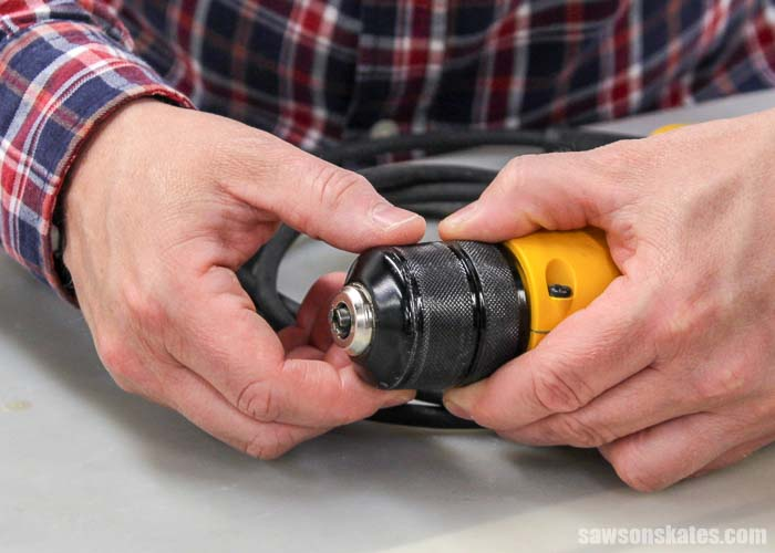 The first step to put a drill bit in a drill is to open the jaws of the chuck