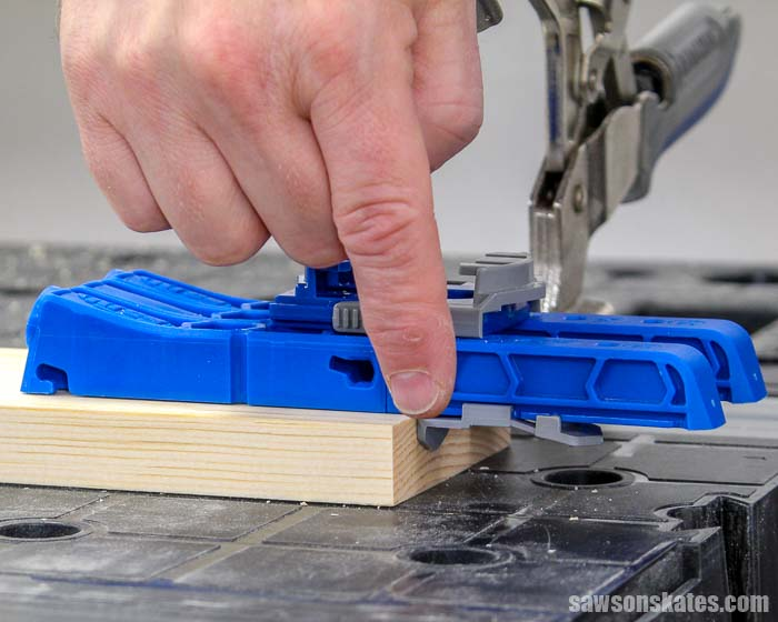 The thickness stops of the Kreg Pocket Hole Jig 320 are pressed against the side of the wood