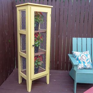 Outdoor plant stand filled with flowers next to an Adirondack chair