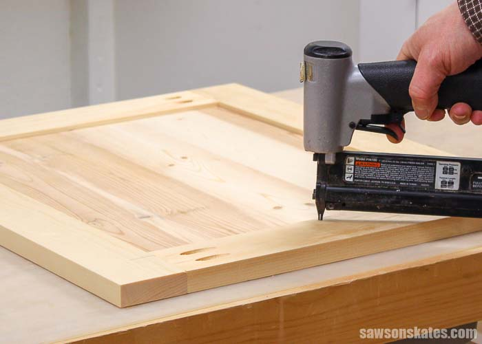 A pin nailer being used to secure the panel in the DIY Shaker cabinet door