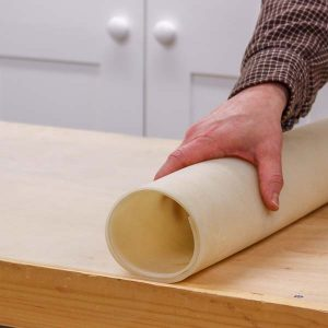 Unrolling a workbench mat on a bench top