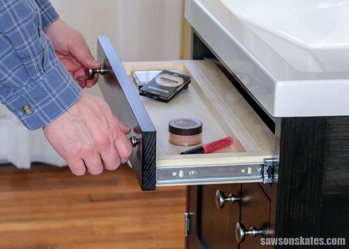 Opening the top drawer of a DIY bathroom vanity