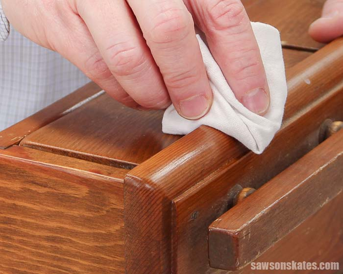 Using a rag to apply a beeswax wood finish to wood shelf
