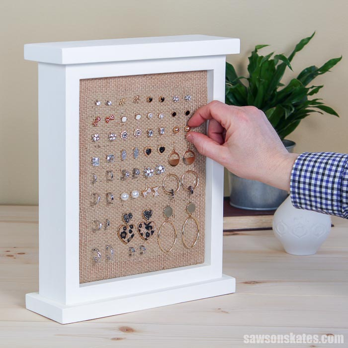 Earrings a jumbled mess? Make this easy DIY earring holder! This wood picture frame-style stand is an attractive way to organize studs, hoops and more.