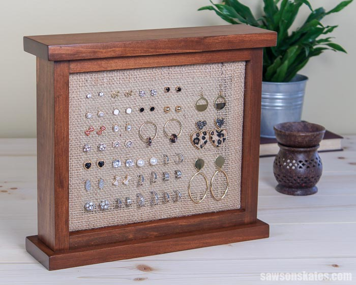 A DIY earring holder stand made with wood and burlap