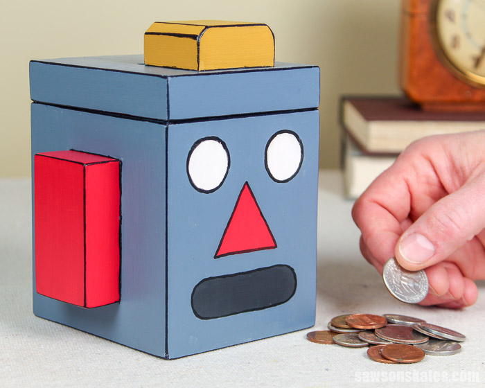 This DIY piggy bank is shaped like a cute robot emoji! It's an easy do it yourself project made with simple supplies like scrap wood and craft paints.