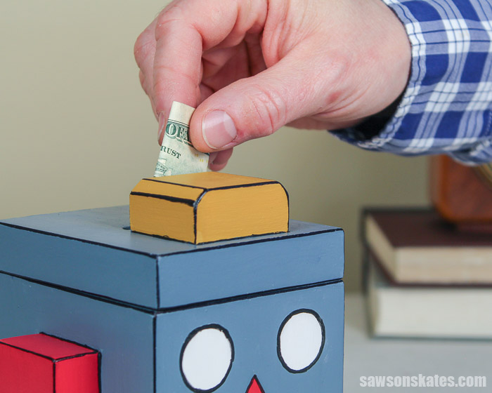 Adding money to an easy to make DIY piggy bank
