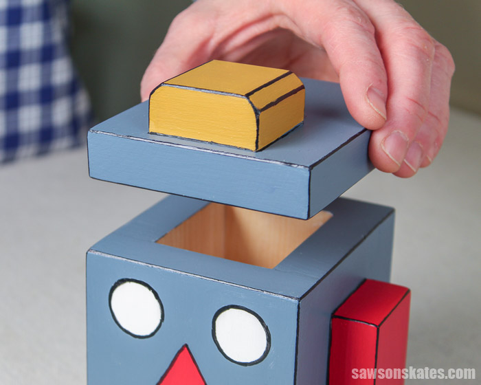 Lifting the lid off of a creative DIY piggy bank shaped like a robot