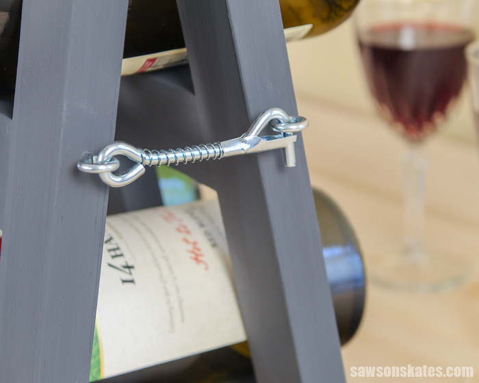 Side view of a modern folding DIY wine rack with a wine glass in the background