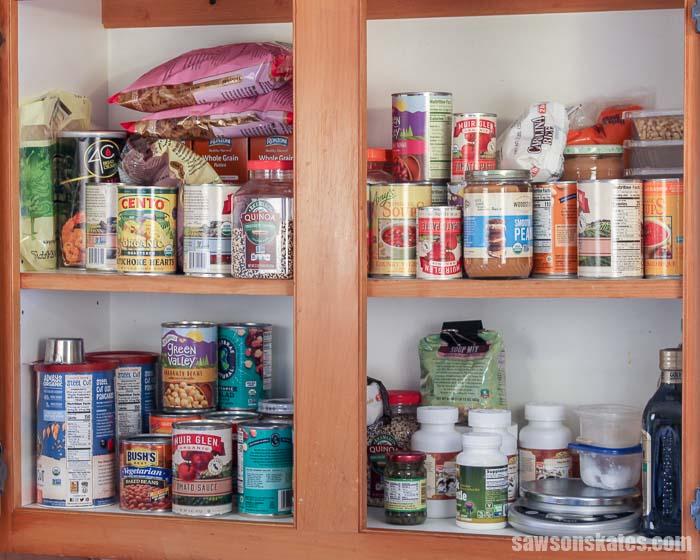 A disorganized kitchen cabinet before adding a DIY cabinet organizer shelf