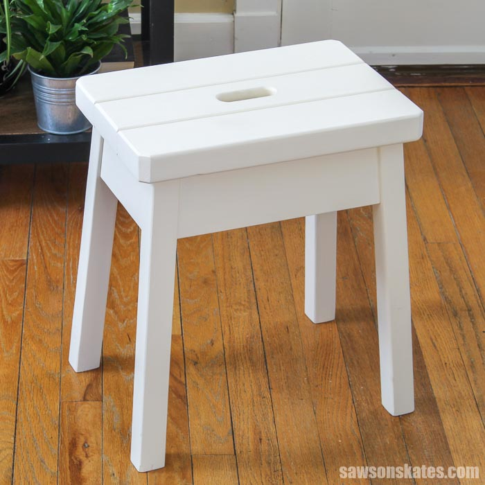 This wood DIY step stool has a simple, rustic design. The angled legs and chunky top give it a farmhouse feel. It's an easy project made with basic tools.