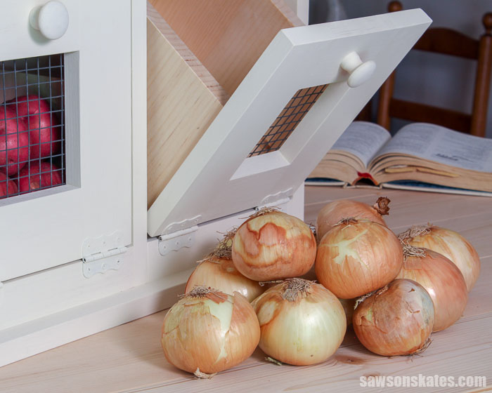 A pile of onions in front of a DIY vegetable storage bin with tilt out drawers