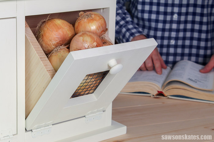 A handmade vegetable storage bin with a tilt out drawer filled with onions