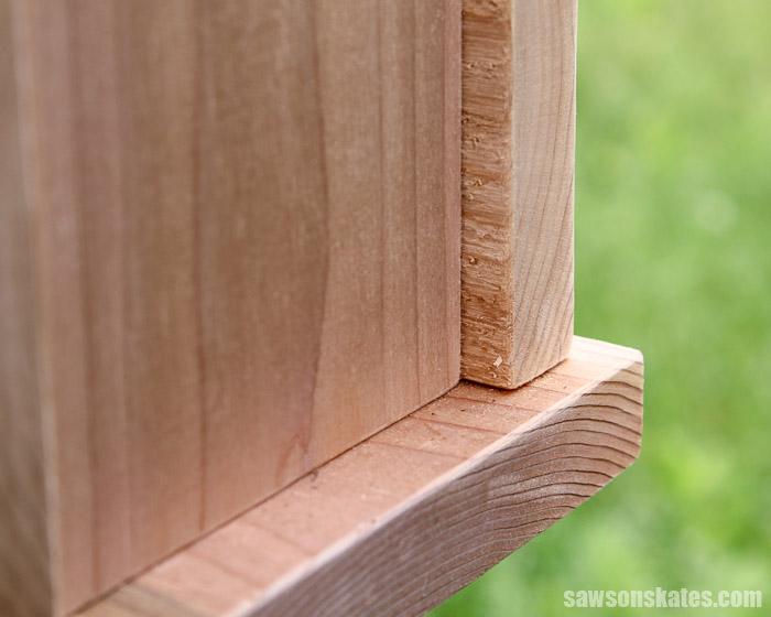 Corner of a DIY bird feeder made with cedar wood