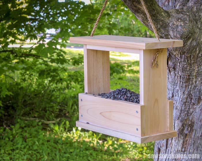 A wood DIY bird feeder filled with birdseed