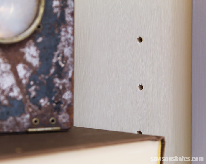 Adjustable shelf pin holes in the side of a DIY chimney cupboard