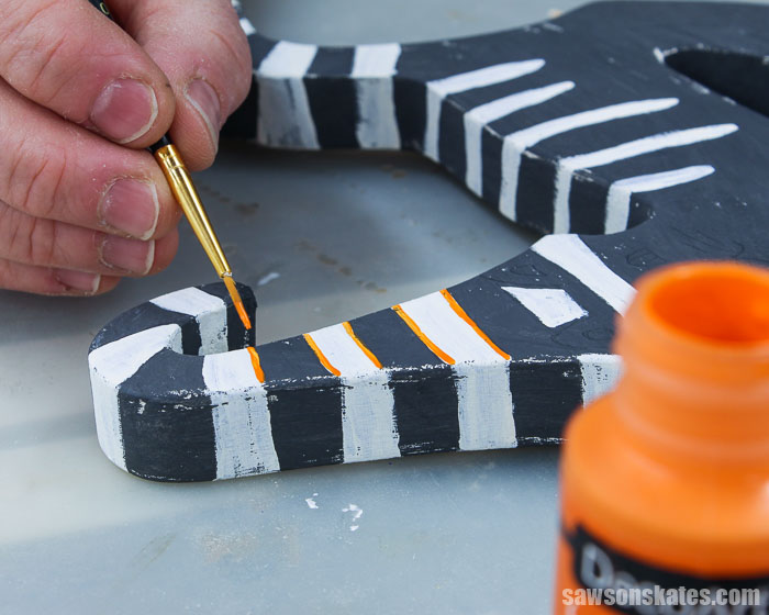 Using a small brush and orange paint to decorate a retro-style Halloween cat