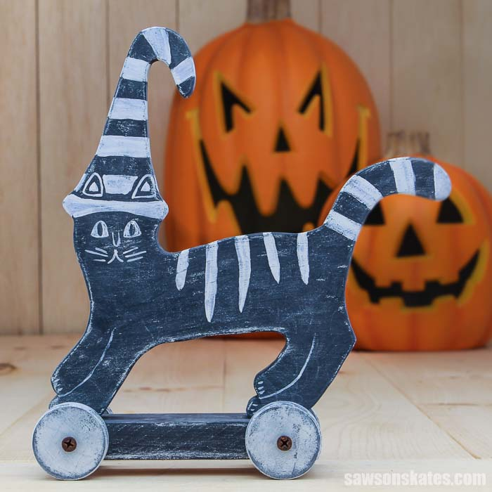 Wooden DIY Halloween cat decoration with two jack o-lanterns in the background