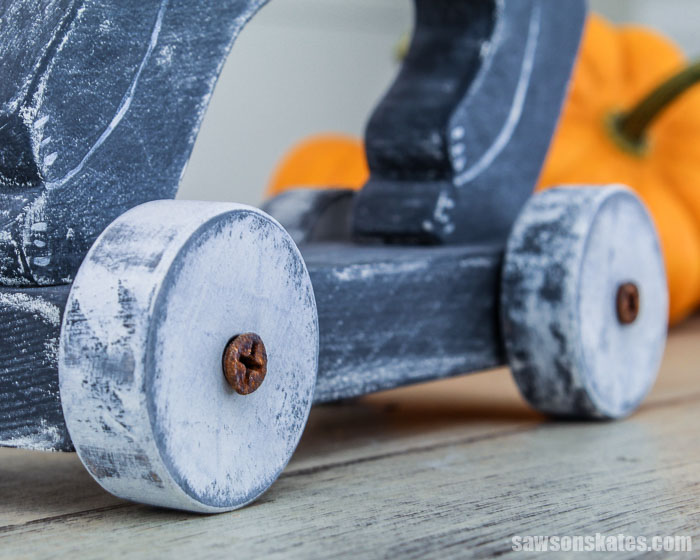 Wooden toy wheels make this DIY Halloween cat decoration look like a retro-style pull toy