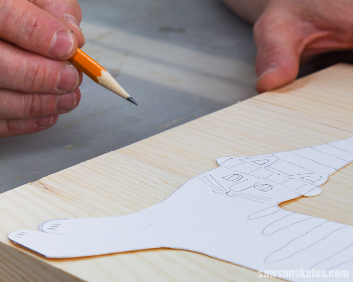 Using a pencil to trace the Halloween cat decoration template onto a piece of wood.
