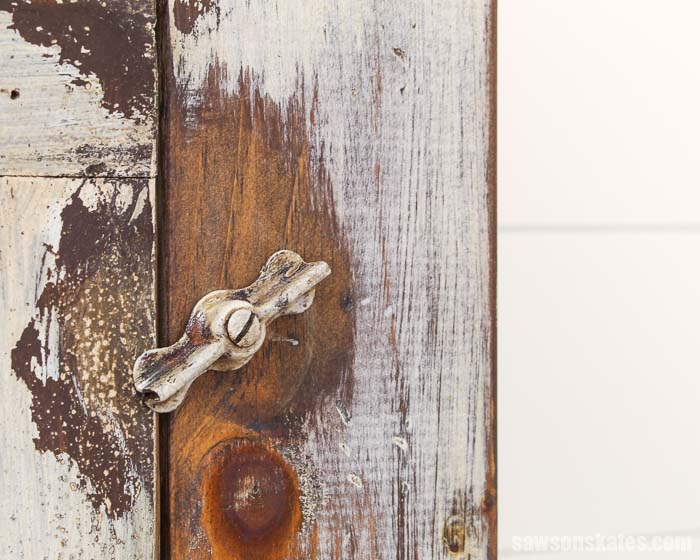 An old latch holds a repurposed window closed in this DIY window cabinet.