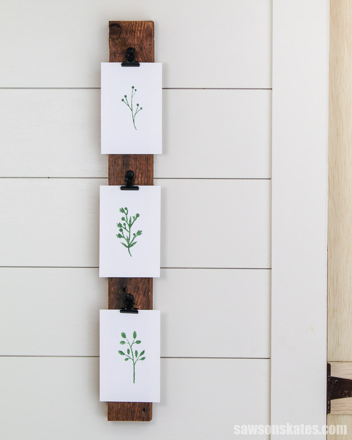 Three pictures displayed vertically on a DIY photo hanger