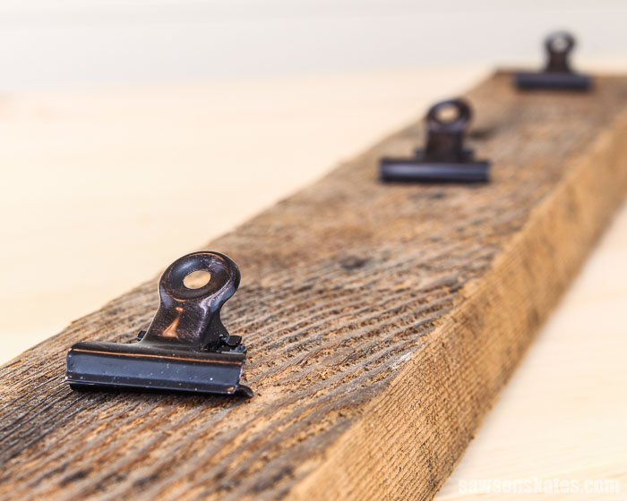 A DIY photo hanger made with a piece of barn wood and three hinge clips