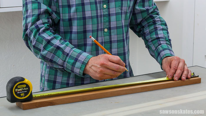 Using a ruler to layout the location for hinge clips on a DIY photo hanger