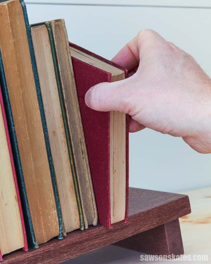 Hand removing a book from a DIY tabletop book rack