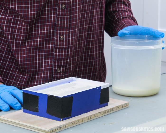 Pouring liquid plastic to make a duplicate piece of trim