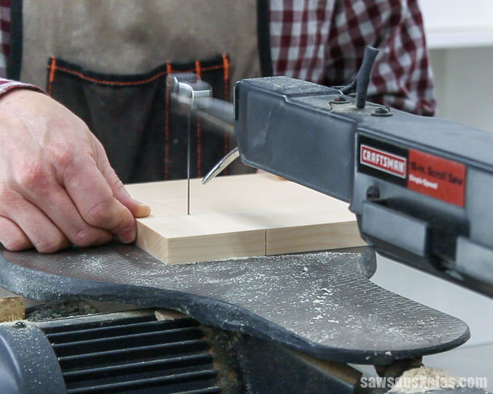 Using a scroll saw to cut out the curved detail on the side of a DIY display cabinet