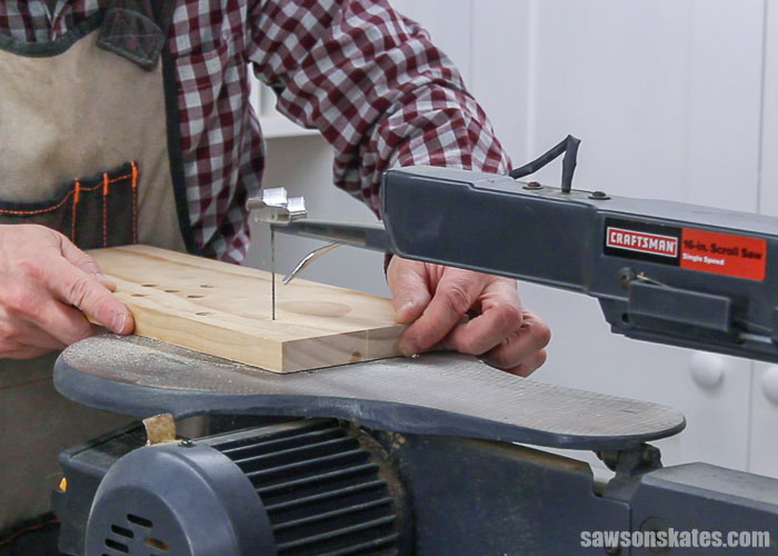 Using a scroll saw to cut out the curved details in the top rail of a DIY display cabinet