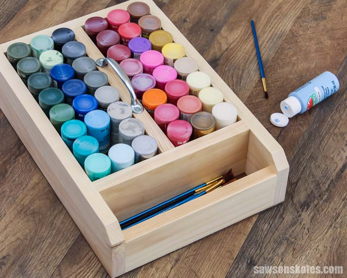 Are your craft paints a jumbled mess? Get them organized now! This DIY craft paint storage caddy is the perfect way to organize 2 oz acrylic paint bottles.