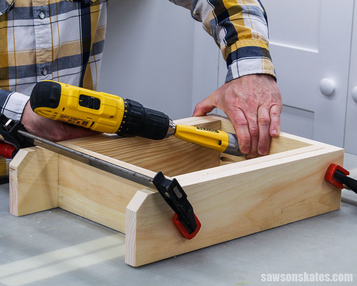 A drill being used to attach the sides of a DIY acrylic paint storage caddy
