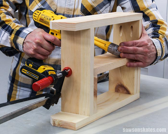 A drill being used to attach the center divider of a DIY a 2 oz paint bottle storage caddy