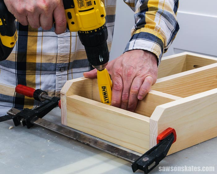 A drill being used to attach the side for a paintbrush storage area in a DIY craft paint organizer