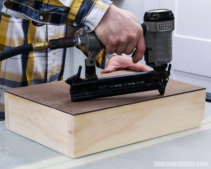 A brad nailer being used to attach the bottom of a DIY acrylic paint storage organizer