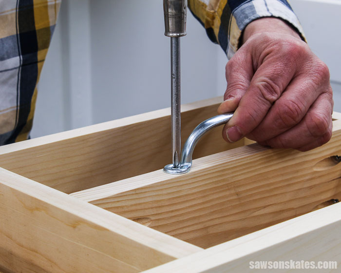 A screwdriver being used to attach a handle to a DIY 2 oz paint bottle storage organizer